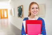 Smiling student holding folders in the hall — Stock Photo