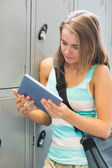 Happy student using her tablet beside lockers — Stock Photo