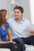 Smiling young couple with bills at home — Stock Photo