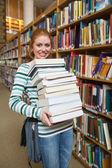 性格开朗的学生持有重型堆站在图书馆的书 — 图库照片