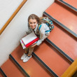 Young student sitting on stairs smiling up at camera — Stock Photo