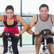 Young man and woman working out at spinning class — Stock Photo #38460633