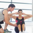 Stock Photo: Trainer assisting womwith pilate exercises in fitness studio