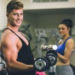 Young man and woman using dumbbells in gym — Stock Photo