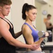 Male trainer helping young womwith dumbbells in gym — Photo #38461117