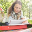 Foto Stock: Pretty smiling student lying on grass studying with her tablet pc