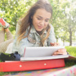 Pretty smiling student lying on grass studying with her tablet pc — Stok Fotoğraf #38461573