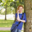 Happy student leaning against a tree talking on the phone — Stock Photo