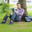 Stock Photo: Smiling student using his tablet pc outside leaning on tree