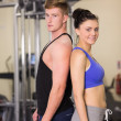 Sporty woman and man standing back to back in gym — Stock Photo #38463355