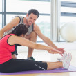 Trainer assisting woman with pilate exercises in fitness studio — Stock Photo #38463685