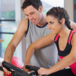 Trainer helping woman work out at spinning class — Stock Photo