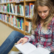Young pretty student sitting on library floor reading book — Stock Photo