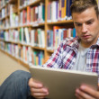 Serious young student sitting on library floor using tablet — Stock Photo #38464539