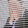 Stock Photo: Businessmwith head in hands in front of blinds in office