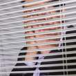 Businessmwith head in hands in front of blinds in office — Stock Photo #38464567