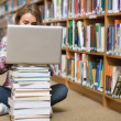 Young student sitting on library floor using laptop on pile of books — Stock Photo #38464573