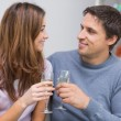 Romantic smiling young couple toasting flutes at home — Stock Photo