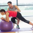Trainer helping young woman with fitness ball at gym — Stock Photo #38464841