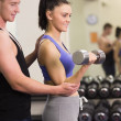 Male trainer helping young womwith dumbbells in gym — Photo #38465185