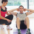 Female trainer watching man do abdominal crunches on exercise mat — Stock Photo #38465475
