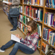Stock Photo: Concentrating student reading book on library floor