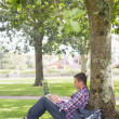 Стоковое фото: Young student using his laptop outside