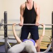 Stockfoto: Trainer helping womto lift barbell bench press in gym