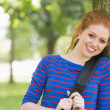 Cheerful redhead student leaning against a tree — Stock Photo