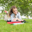 Stock Photo: Smiling young student studying on the grass