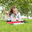 Smiling young student studying on the grass — Stock Photo