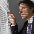 Serious businessman peeking through blinds in office — Stock Photo #38467373