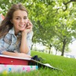 Foto Stock: Young pretty student lying on grass on phone