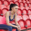 Smiling toned woman sitting on chair in the stadium — Foto Stock