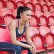 Smiling toned woman sitting on chair in the stadium — Stockfoto