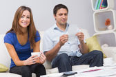 Portrait of a smiling couple with bills at home — Stock Photo