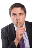 Green eyed businessman with finger to his lips — Stock Photo