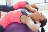 Due donne che si estende su palle di fitness in palestra in forma — Foto Stock