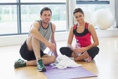 Woman and man with water bottles sitting at gym — Stock Photo