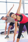 Two sporty people stretching hands at yoga class — Stock Photo