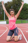 Toned young woman cheering on the running track — Stock Photo