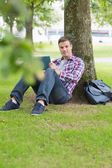 Smiling student using his tablet pc outside leaning on tree — Stock Photo