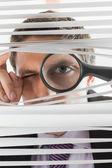 虫眼鏡でブラインドを覗く実業家 — ストック写真