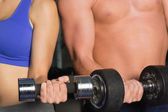 Mid section of a shirtless man and woman with dumbbells — Stock Photo