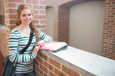 Redhead student smiling at camera in the corridor — Stock Photo