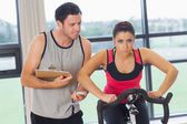 Trainer watching woman work out at spinning class — Stock Photo