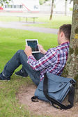 Student using his tablet pc outside leaning on tree — Stock Photo