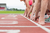 Side view of cropped people ready to race on track field — Stock Photo