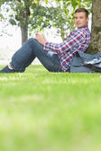 Happy student using his tablet to study outside — Stock Photo