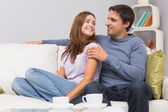 Relaxed couple sitting on sofa at home — Stock Photo